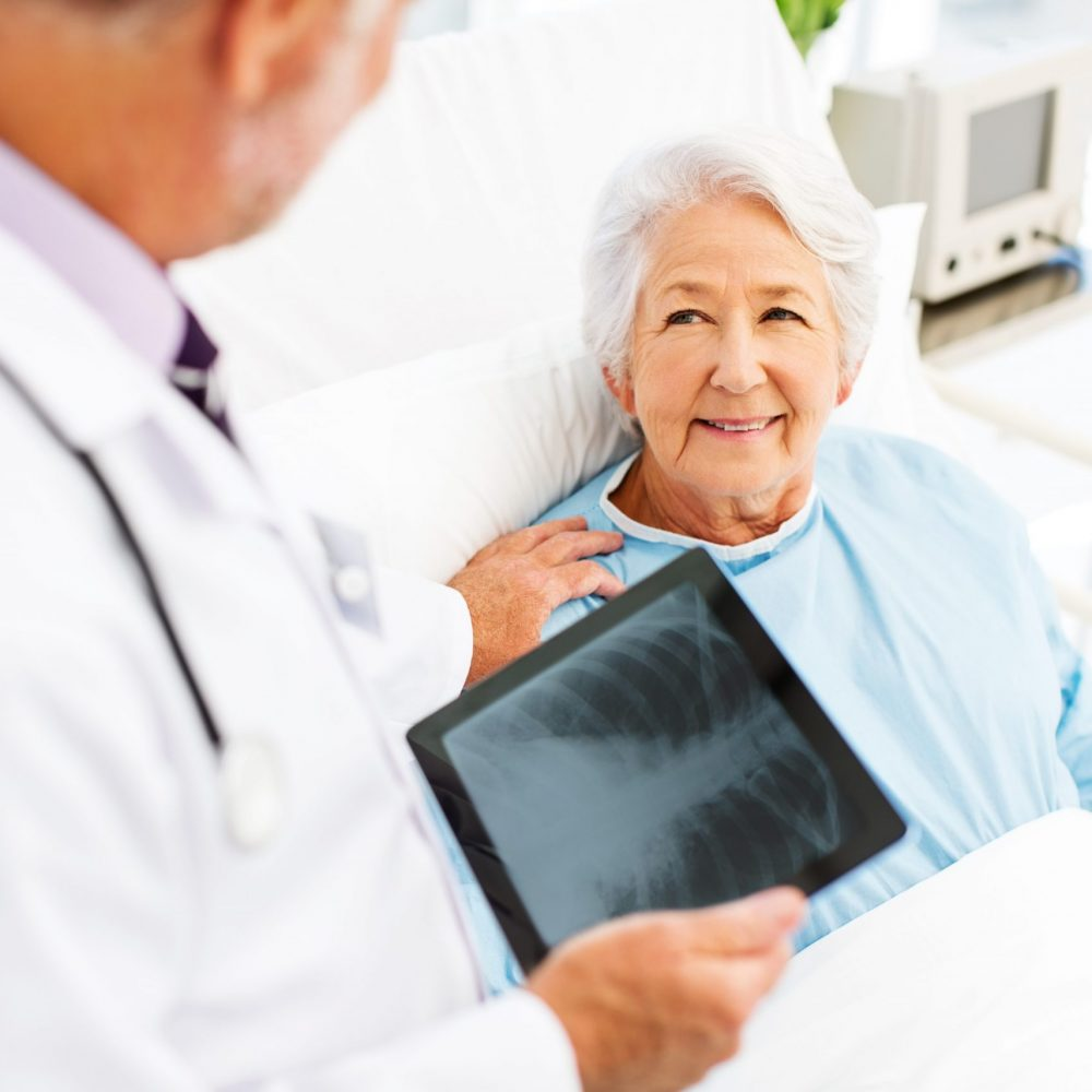 Woman Looking At Doctor With X-Ray On Digital Tablet