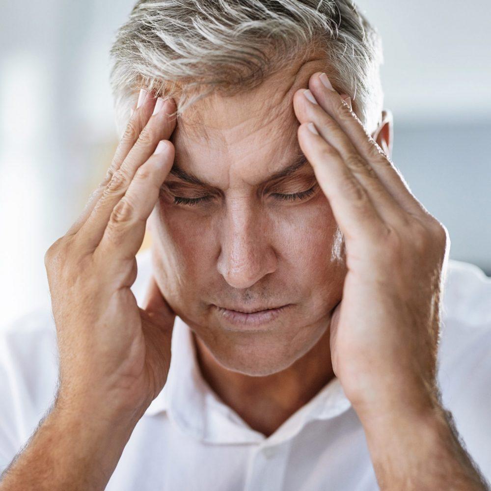 mature businessman suffering with a headache