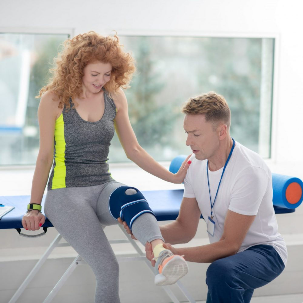 Male physiotherapist holding and examining leg of female patient