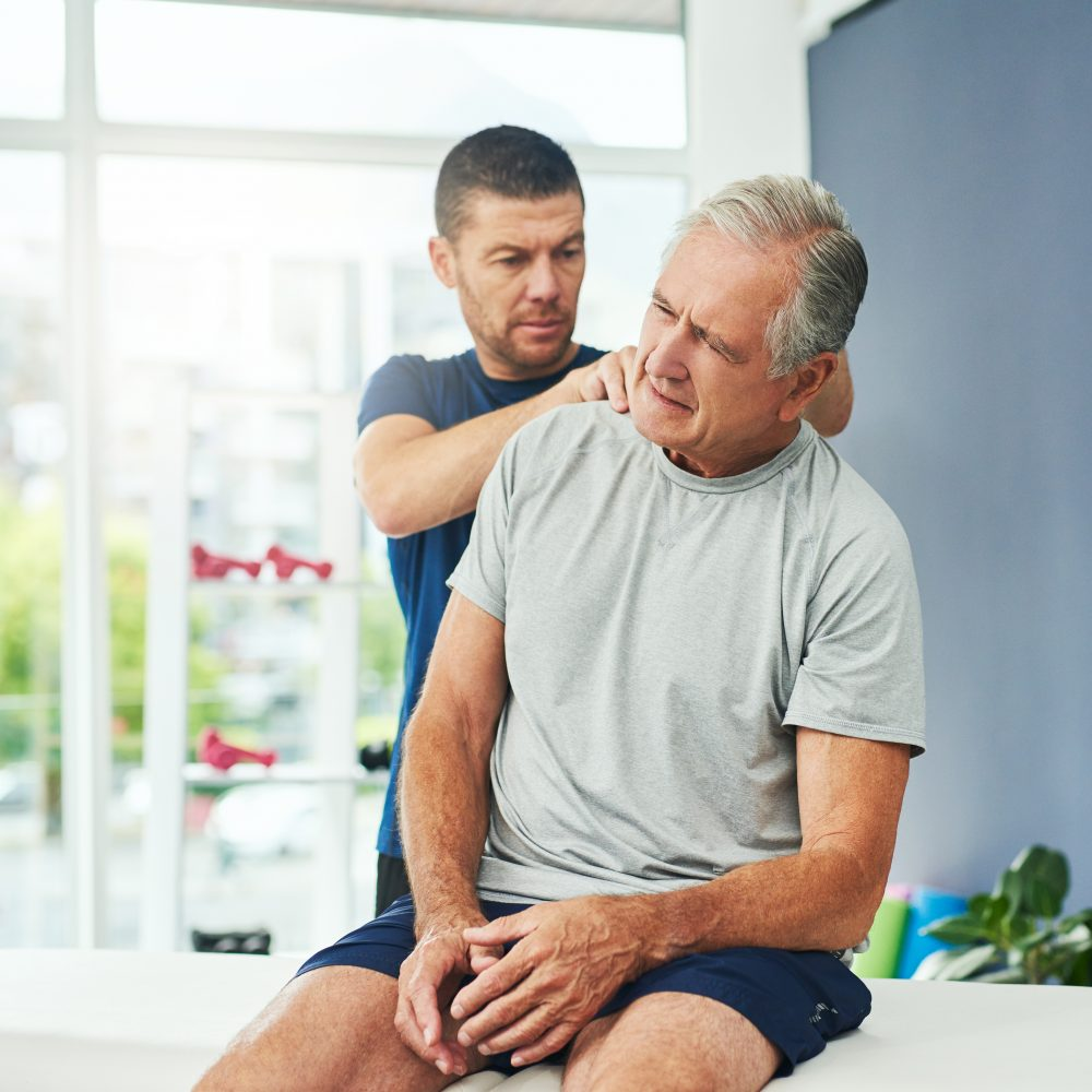 male physiotherapist doing a consultation and assessment with a senior patient