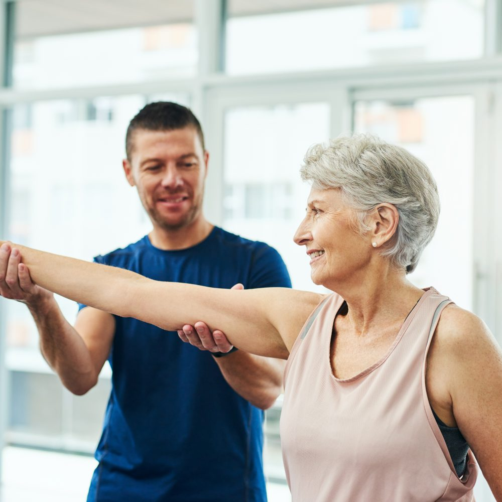 Physical therapist helping woman with arm